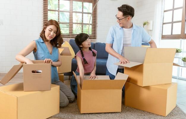Feliz família asiática embalando a caixa de papelão durante a mudança para a nova casa.