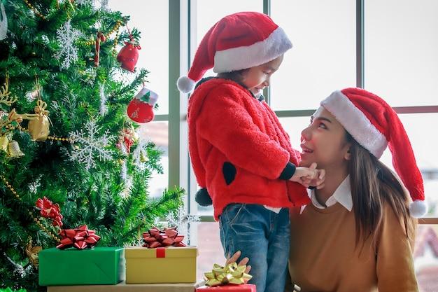 Feliz família asiática mãe e filha com chapéu de papai noel vermelho e branco e camisola sorrindo brincando juntos perto de pinheiro de natal com itens de decoração de brilho e caixas de presente na noite de natal.