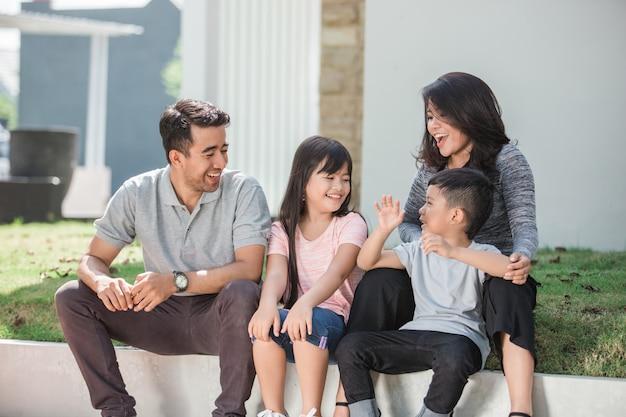 Feliz família asiática na frente de sua casa