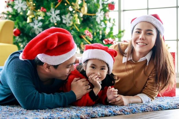 Feliz família asiática pai, mãe e filha veste uma camisola com chapéu de papai noel vermelho e branco deitou-se no chão do carpete, comemorando a véspera de natal juntos na decoração da frente pinheiro de natal.