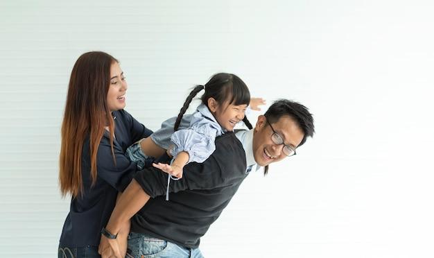 Feliz família asiática se abraçando na sala de estar de casa.