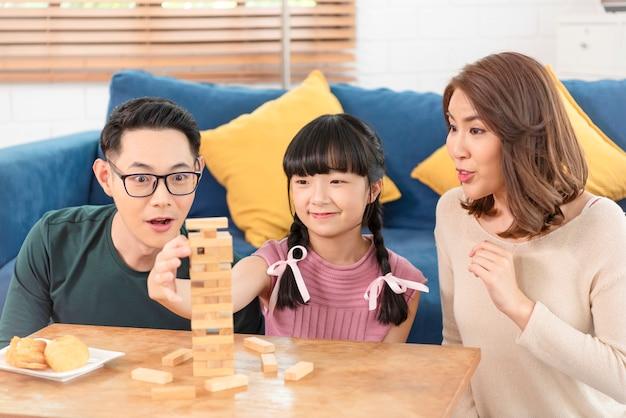 Feliz família asiática se divertindo jogando o jogo de blocos na sala de estar em casa.