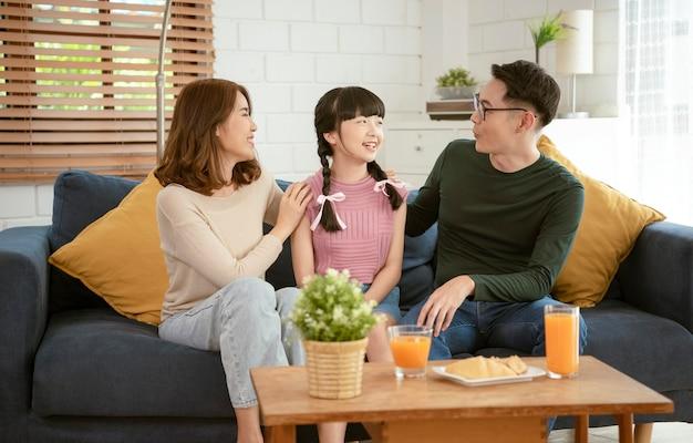 Feliz família asiática sentados juntos no sofá na sala de estar em casa.
