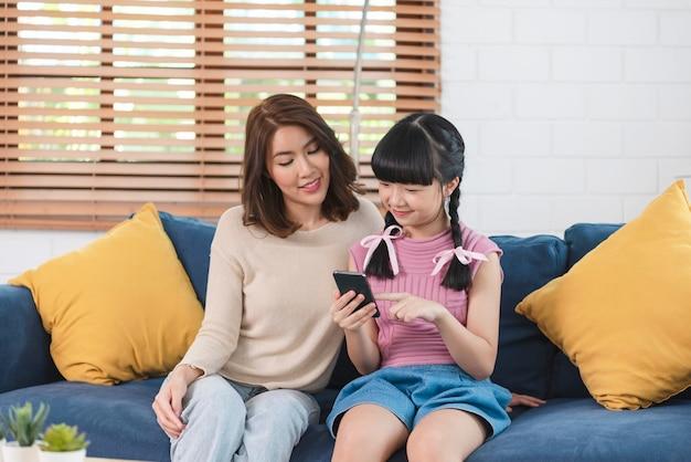 Feliz família asiática usando smartphone juntos no sofá na sala de estar em casa.
