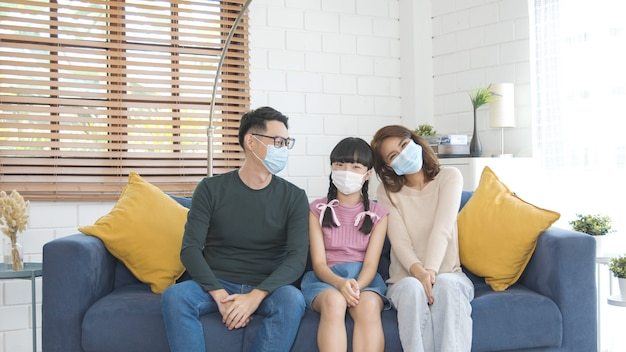 Feliz família asiática usando uma máscara para se proteger contra vírus na sala de estar de casa.