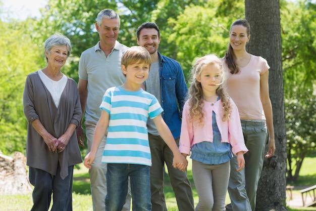 Feliz família estendida em pé no parque
