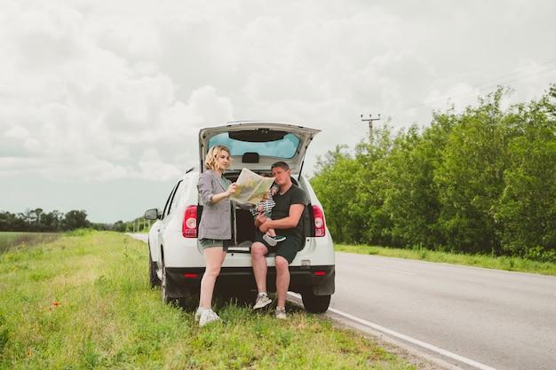 Feliz família fofa de pai, mãe e filho estão viajando de carro e pararam na beira da estrada para ver o mapa.
