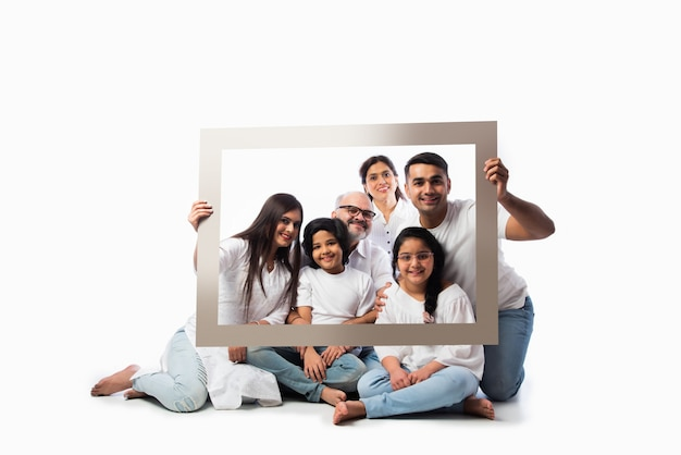 Feliz família indiana asiática multigeracional de seis pessoas olhando através de uma moldura vazia, em pé ou sentado contra um fundo branco, usando panos brancos e jeans azul