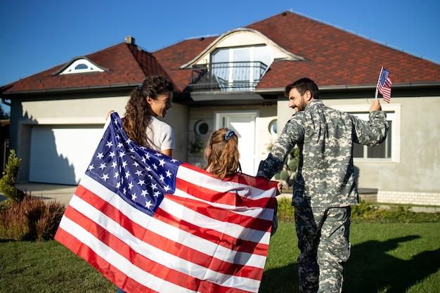 Feliz família militar carregando a bandeira americana e dando as boas-vindas ao soldado pai em casa.