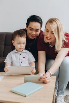 Feliz família multicultural. homem asiático e mulher branca com seu filho assistindo vídeo no tablet e telefone.