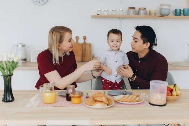 Feliz família multicultural. pai asiático e sua esposa loira caucasiana tomar café da manhã com seu lindo filho na cozinha.