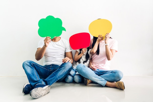 Feliz família pai e mãe com a filha segurando um ícone de bolha do discurso