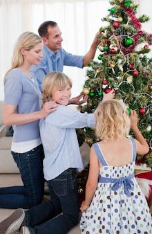 Feliz família pendurado decorações em uma árvore de natal