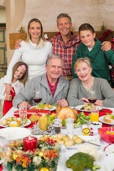 Feliz, família prolongada, olhando câmera, em, natal, tempo