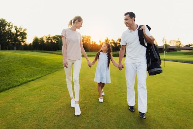 Feliz família unida de golfistas caminha após o jogo.