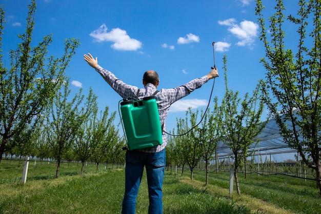 Feliz fazendeiro agrônomo com pulverizador e mãos levantadas celebrando o sucesso no pomar de maçã