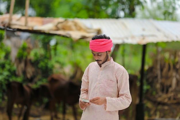 Feliz fazendeiro indiano contando dinheiro em casa.