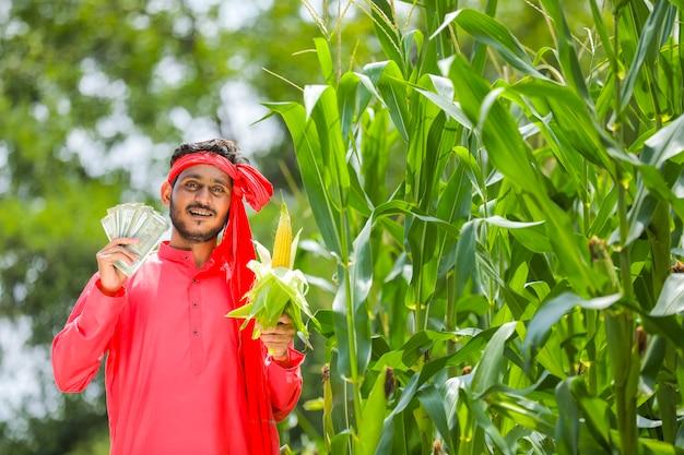 Feliz fazendeiro indiano mostrando milho e moeda indiana em um campo de milho verde
