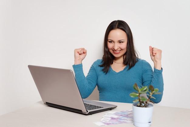 Feliz feliz contente mulher sentada no seu laptop. o conceito de sucesso, freelancer, ganhos remotos, informática, loteria, ganhar