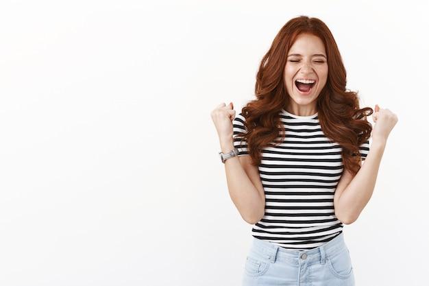 Feliz feliz e animada garota jovem com cabelo comprido vermelho em uma camiseta listrada vencendo, se tornando campeã, erguendo o punho em comemoração, gesto de triunfo, olhos fechados e sorrindo emocionado, alcance o sucesso