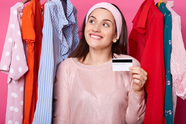 Feliz fêmea detém um cartão de crédito e sorri. jovem comprador sente gosma, morde o lábio. mulher atraente tem cartão de plástico ilimitado para a compra de vestidos em grande shopping center. conceito de compras e moda.