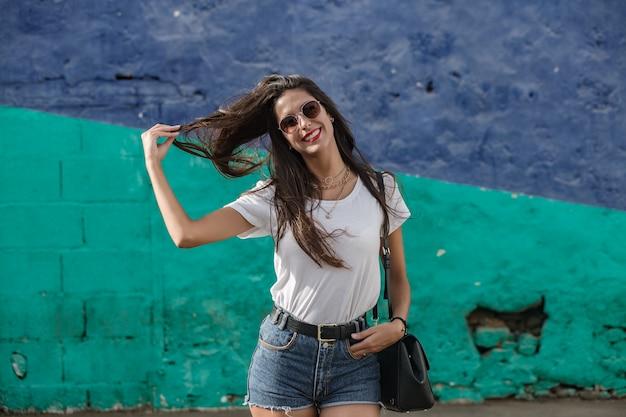 Feliz fêmea em pé pela parede, puxando o cabelo