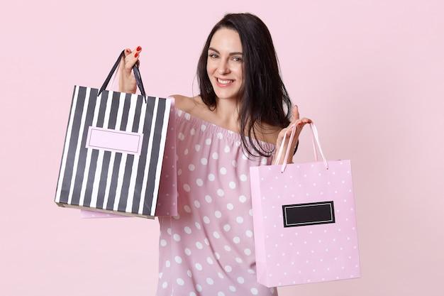 Feliz fêmea jovem viciada em compras com expressão facial satisfeita, vestida com vestido de bolinhas de verão, detém sacolas de compras, se alegra comprando roupas novas, poses em rosa. mulher com pacotes