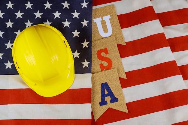 Feliz feriado federal dia do trabalho construção ferramentas capacete amarelo sobre bandeira americana.