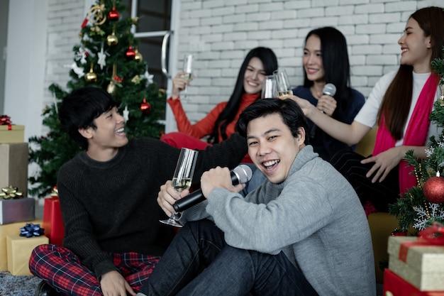 Feliz festa de jovens asiáticos com beber vinho e cantar uma música em casa para comemorar o festival de natal. celebração de ano novo em casa. feliz natal e boas festas de gangue teen thai.