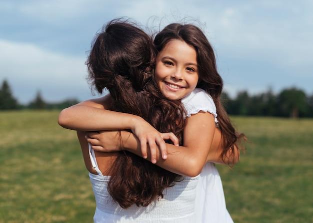 Feliz, filha, abraçando, mãe, ao ar livre