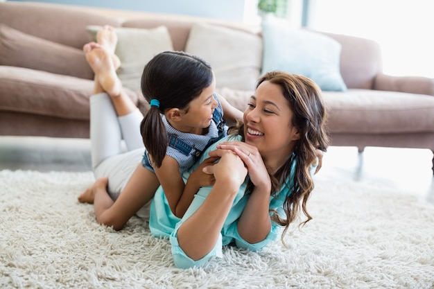 Feliz filha e mãe interagindo uns com os outros enquanto estava deitado no tapete