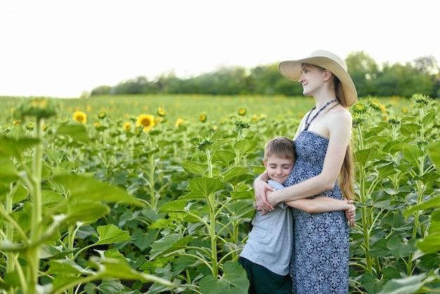 Feliz filho pequeno abraça a mãe grávida em pé em um campo de girassóis florescendo