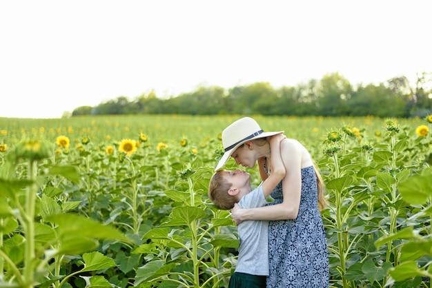 Feliz filho pequeno beijando a mãe grávida em pé no campo de girassóis florescendo