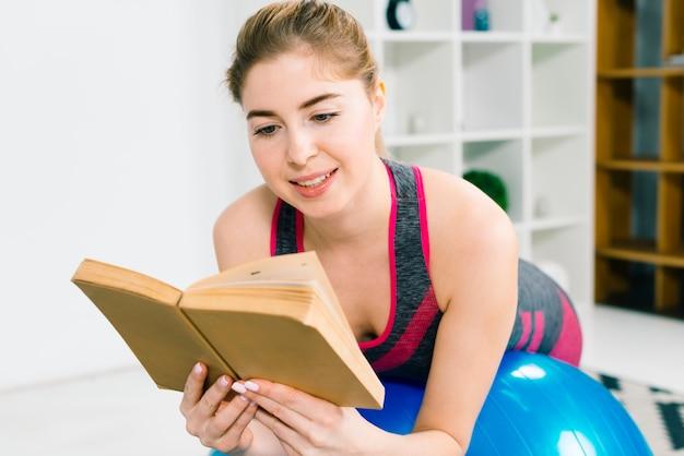Feliz fitness jovem mulher deitada na bola de pilates, lendo o livro