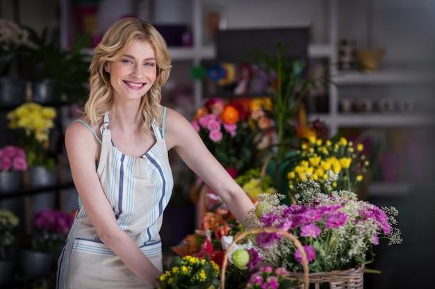 Feliz florista feminina em pé na loja de flores