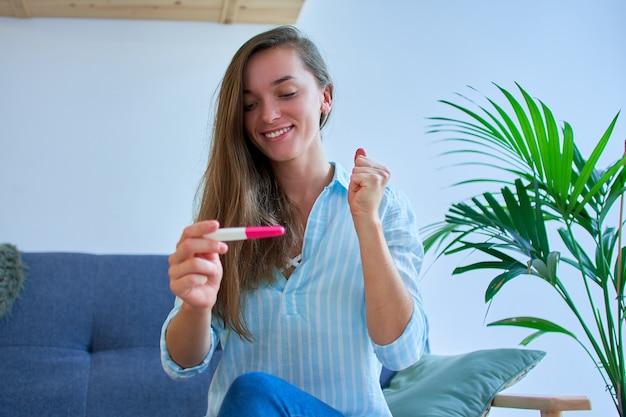 Feliz fofa jovem sorridente e satisfeita se alegra com um resultado positivo no teste de gravidez
