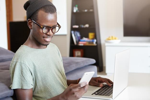 Feliz freelancer preto casual, sentado à mesa na frente do computador portátil enquanto trabalhava no projeto em casa, sorrindo amplamente, lendo a mensagem