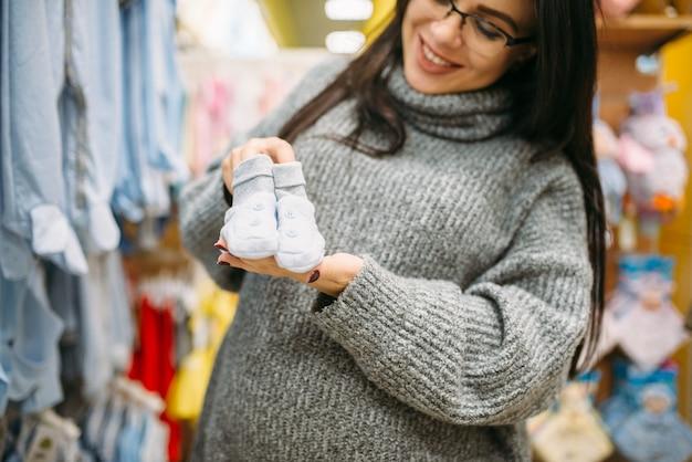Feliz futura mãe compra roupas de criança