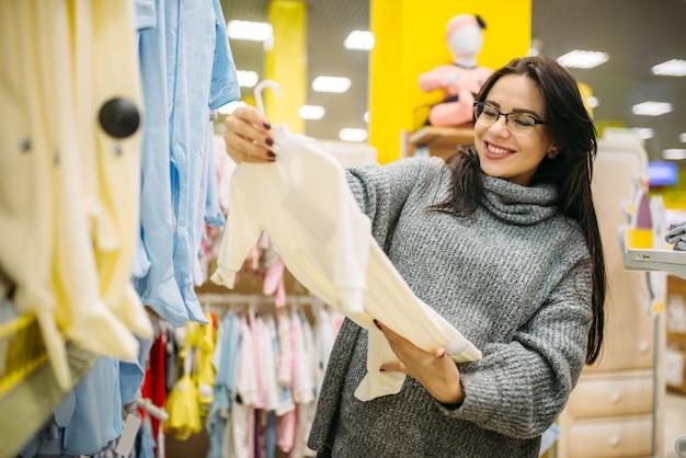 Feliz futura mãe escolhendo roupas na loja