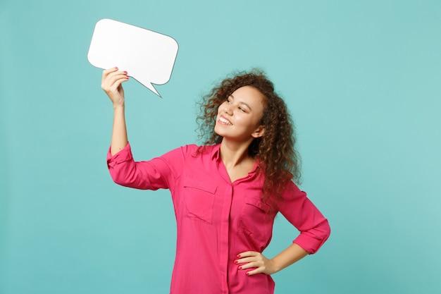 Feliz garota africana com roupas casuais segurando vazio em branco say nuvem, balão de fala isolado no fundo da parede azul turquesa no estúdio. conceito de estilo de vida de emoções sinceras de pessoas. simule o espaço da cópia.