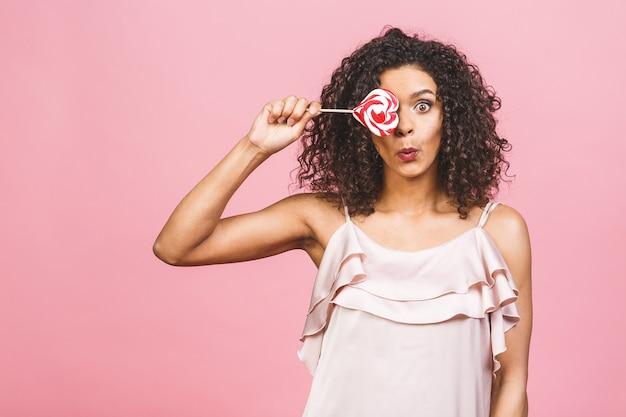 Feliz garota afro americana sexy comendo pirulito. beleza glamour modelo mulher segurando rosa doce colorido pirulito doce, isolado no fundo rosa. doces.