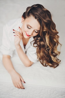 Feliz garota bonita com cabelo morena brilhante e maquiagem sorrindo para baixo.