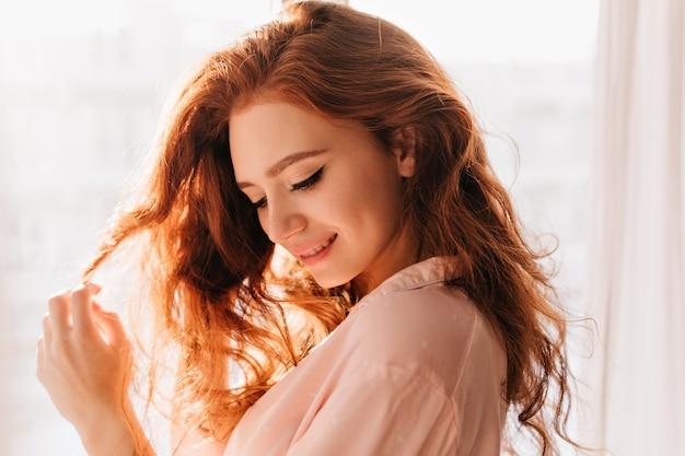 Feliz garota caucasiana brincando com seus cabelos ondulados. foto interna de uma senhora deslumbrante apreciando a sessão de fotos em casa.