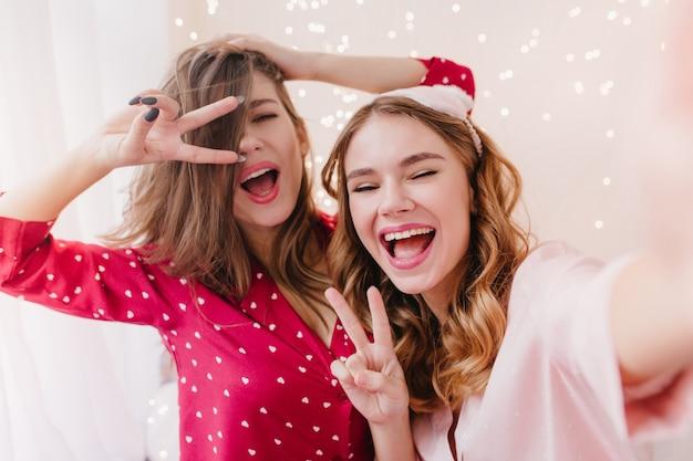 Feliz garota de cabelos escuros brincando durante a sessão de fotos da manhã. rindo mulher encantadora de pijama rosa fazendo selfie com a amiga.