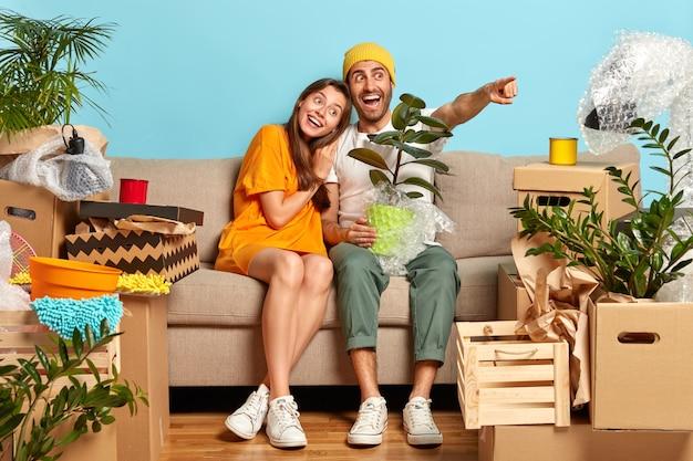 Feliz garota de cabelos escuros se inclina sobre o ombro do namorado que segura embrulhado em um vaso de planta doméstica