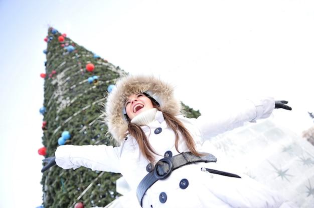 Feliz garota de pé junto à árvore de natal