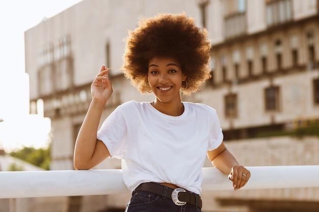 Feliz garota de pele escura em uma camiseta branca em uma caminhada de verão
