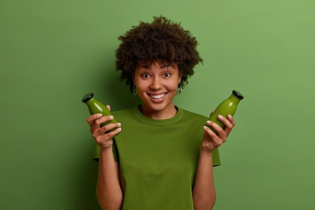 Feliz garota de pele escura segura garrafas de vidro com smoothie vegetal de desintoxicação verde cru, leva um estilo de vida saudável, mantém a dieta vegetariana, se sente revigorada e feliz. foto monocromática. pessoas e bem-estar