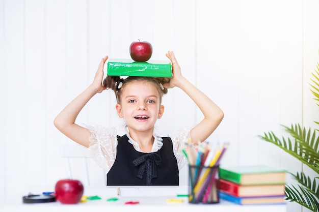 Feliz garota esperta em uniforme escolar segurando um livro e uma maçã vermelha na cabeça