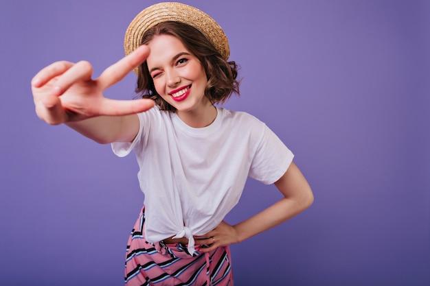 Feliz garota europeia com olhos escuros, posando em um chapéu de palha da moda. foto interna do modelo feminino sensual, com cabelo curto em pé na parede roxa e rindo.